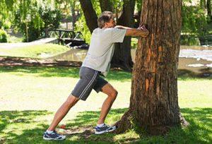 man_stretching_at_tree